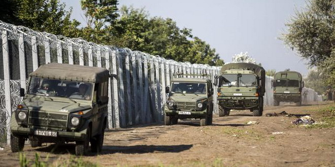 Military vehicles drive along the border fence between Hungary and Serbia, near Roszke, 180 kms southeast from Budapest, Hungary, Monday, Sept. 14, 2015. European Union interior ministers meet for emergency migration talks on Monday, a day after Germany reintroduced checks at its border with Austria to stem the continuing flow of refugees. (Balazs Mohai/MTI via AP)