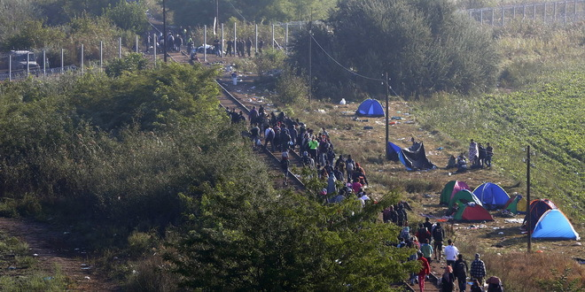 Migrants arrive at the border line between Serbia and Hungary near Roszke, southern Hungary, Sunday, Sept. 13, 2015. Hundreds of thousands of Syrian refugees and others are still making their way slowly across Europe, seeking shelter where they can, taking a bus or a train where one is available, walking where it isn't. The latest string of walkers made their way Friday from the Hungarian border across Austria toward the capital, Vienna. (AP Photo/Matthias Schrader)