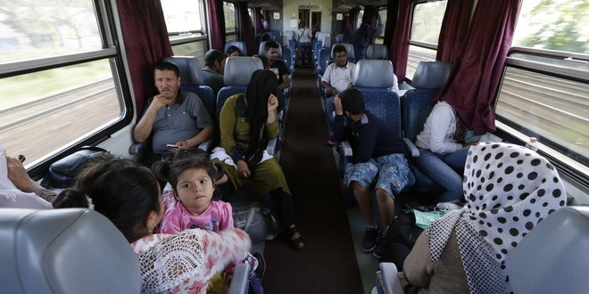 People sit on a train as hundreds of migrants left the Keleti Railway Station in Budapest, Hungary, Thursday, Sept. 3, 2015. Over 150,000 migrants have reached Hungary this year, most coming through the southern border with Serbia. Many apply for asylum but quickly try to leave for richer EU countries. (AP Photo/Petr David Josek)
