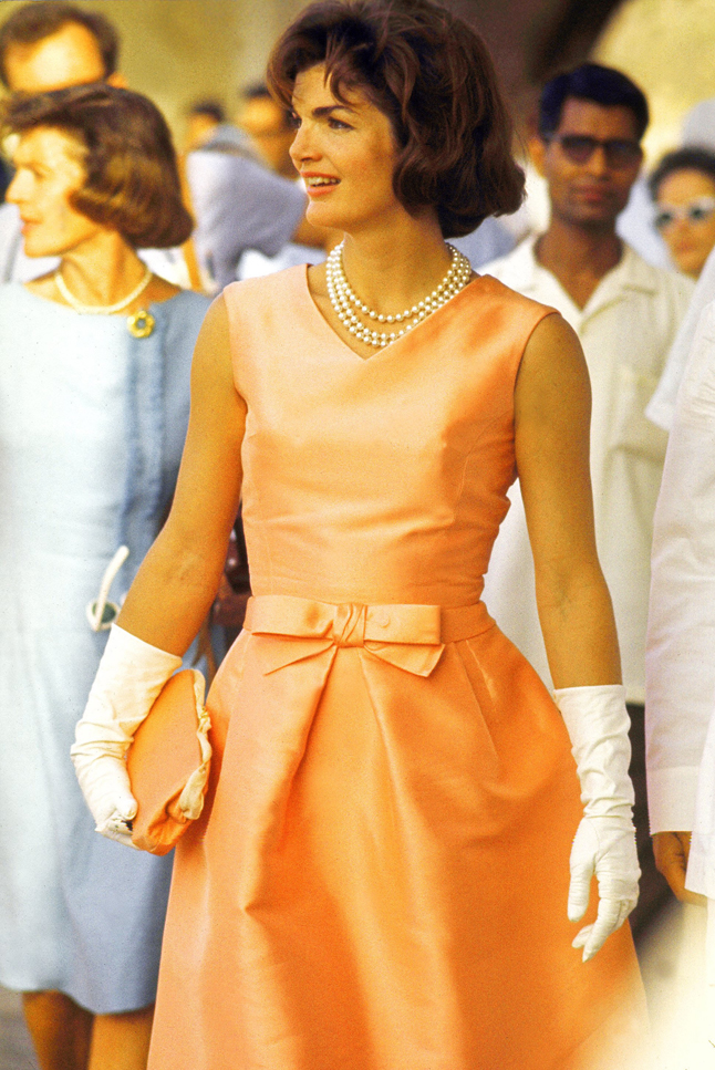 First Lady Jackie Kennedy wearing a fitted silk apricot dress and triple strand of pearls, walking through crowds at Udaipur during visit to India.  (Photo by Art Rickerby//Time Life Pictures/Getty Images)