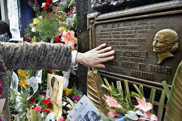 A Peronist supporter touches Maria Eva Duarte de Peron's tomb, 26 July 2002 on the 50th Anniversary of her death. Eva Peron, known as Evita, second wife of Argentine President Juan Domingo Peron, was a radio and screen actress before her marriage in 1945. She became a powerful political influence and a mainstay of Peron's government. She was idolized by the working class, and after her death, in Buenos Aires, support for her husband's government waned. AFP PHOTO / Daniel GARCIA